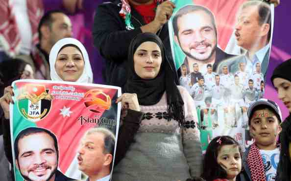 Jordanian fans holds a poster bearing po