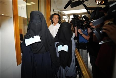 French businessman Rachid Nekkaz stands next to Halima and Imen after he paid their fines for wearing a niqab in Brussels